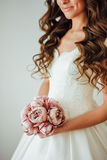 Bride.Young fashion model with perfect skin and make up, white background, curly hair, flowers Royalty Free Stock Images