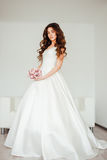 Bride.Young fashion model with perfect skin and make up, white background, curly hair, flowers Stock Photography