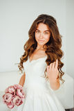 Bride. Young fashion model with perfect skin and make up, white background, curly hair, flowers Stock Photography
