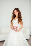 Bride.Young fashion model with perfect skin and make up, white background, curly hair, flowers. Bride.Young fashion model with perfect skin and make up, white stock photography