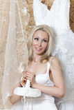 Bride, the young woman with blonde  long hair  dreams of a wedding near a wedding dress Stock Photos