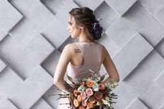 The Bride or Young woman in wedding dress standing back to camera holding bouquet.  Royalty Free Stock Photography