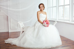 The Bride. Young women with wedding dress in very bright room, Stock Photo