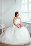 The Bride. Young women with wedding dress in very bright room, Stock Images