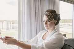 Bridechecking make-up in hand mirror. Bride looking at herself in hand mirror by hotel window Stock Photos
