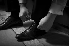 Bridegirl binds his shoes in black and white. royalty free stock photography