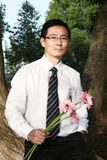 Bridegroom. Holding pink daisy bouquet at the park stock photography
