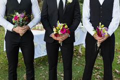 Bridegroom and best man standing with bouquet of flowers in garden. Mid-section of bridegroom and best man standing with bouquet of flowers in garden royalty free stock photos