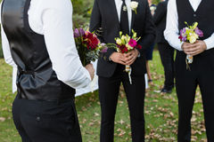 Bridegroom and best man standing with bouquet of flowers in garden. Mid-section of bridegroom and best men standing with bouquet of flowers in garden stock photos