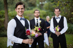 Bridegroom and best man standing with bouquet of flowers in garden. Portrait of bridegroom and best men standing with bouquet of flowers in garden royalty free stock image