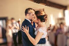 The bridegroom embraces the bride during the wedding dance. The bridegroom in a blue jacket embraces the bride during the wedding dance stock photo