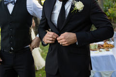Bridegroom buttoning a wedding suit. Mid-section of bridegroom buttoning a wedding suit royalty free stock photo