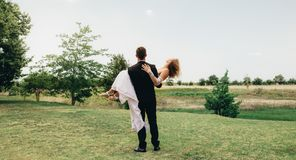 Bridegroom lifting up his bride at park. Bridegroom carrying his bride in his arms and standing outside. Rear view of newly wed couple celebrating their marriage Royalty Free Stock Image