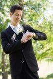 Bridegroom checking time in garden Stock Photos