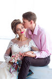 The bridegroom embraces the bride and kissing. The groom in a pink shirt hugs the bride and kisses Royalty Free Stock Photo
