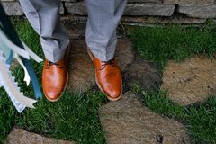 The bridegroom in an expensive luxurious plaid gray suit and leather brown shoes. Man`s feet on a rainy cloudy day on a backgroun stock photography