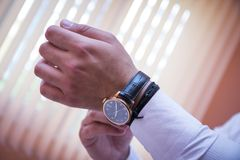A businessman touches and adjusts his luxury clock. Bridegroom fixes the watch strap royalty free stock photography