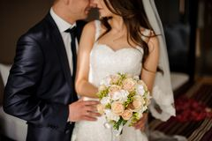Bridegroom is going to kiss charming bride with a bouquet. Stylish bridegroom is going to kiss charming brunette bride with a bouquet of romantic roses royalty free stock photography