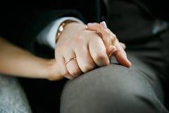 The bridegroom holds the bride`s hand. Groom holds tightly to the bride`s hand after the wedding Stock Photo