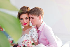 The bridegroom hugs the bride from behind. The groom in a pink shirt hugs the bride from behind Stock Image