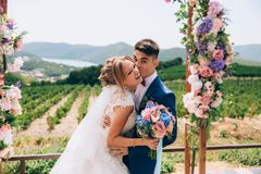 The bridegroom hugs and kisses her bride. The girl laughs because she heard a good joke. Lovers at the wedding indulge. And have fun Royalty Free Stock Photography
