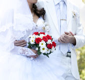 Bridegroom keeping bride hand. And beautiful red roses wedding flowers bouquet at background Royalty Free Stock Images