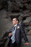 Bridegroom looks away to the background of rocks Stock Photos