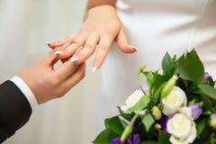 Bridegroom Put the Wedding Ring on bride finger. On flower background stock photos