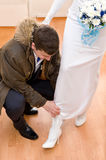 Bridegroom puts shoes on bride's feet Stock Photos