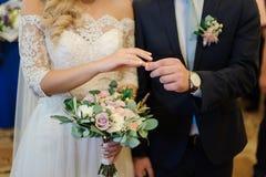 Bridegroom putting a wedding ring on the bride finger. Bridegroom putting a wedding ring on the blonde bride finger standing in the wedding palace stock photos