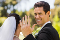 Bridegroom showing wedding ring to the camera in park Stock Images