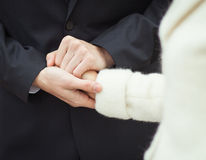 A bridegroom squeezeing bride's hand Stock Image