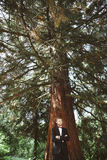 Bridegroom standing under tree Royalty Free Stock Image