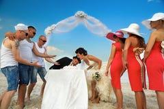Bridegroom trying to take a bite of wedding cake. Royalty Free Stock Photo