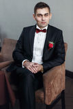 Bridegroom in tuxedo sits in the brown chair. A stock photo