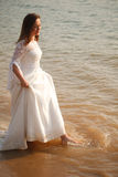 Bride is walking in water Stock Photography