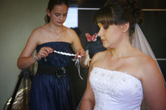 Bridemaid helps to put on a necklace. Teo persons portrait Stock Images