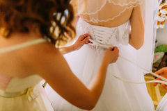 Bridemaiden helps dressing bride her white wedding dress Royalty Free Stock Photo