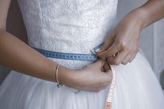 Bridemeasuringher waist before the wedding day stock photography