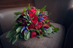 Brides bouquet of red roses before the wedding lies on a brown background. Brides bouquet of red roses before the wedding, lies on a brown background Royalty Free Stock Image