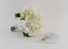 Brides Bouquet, Rings, and Handkerchief. Ivory and cream brides bouquet, wedding rings, and white and blue handkerchief on white background Royalty Free Stock Photo