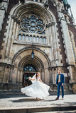 Brides dancing on the background of a Gothic church Stock Photography