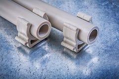 Brides de tuyau d'eau-tuyaux de plastique sur la construction métallique de fond photo stock