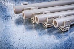 Brides de tuyau d'eau-tuyaux de PVC sur la construction métallique de fond photographie stock libre de droits