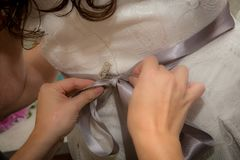 Brides Dress getting tied royalty free stock photography