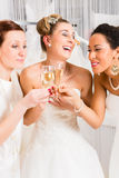 Brides drinking champagne in wedding shop Royalty Free Stock Photos
