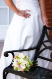 Brides flowers. A bride standing by a bench that her flowers are resting on Royalty Free Stock Image