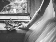 Brides hand holding autumn leaf while sitting in front of window Royalty Free Stock Images