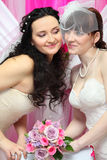 Brides look at each other and hold bouquet Stock Image