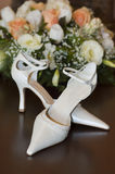 Brides shoes and flowers. Wedding bouquet and shoes. Sharpness is on the shoes Royalty Free Stock Images